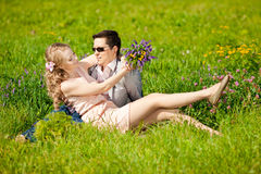 Happy young adult couple in love on the field. Two,  man and wom Royalty Free Stock Photo