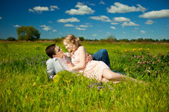 Happy young adult couple in love on the field. Two,  man and wom. Happy young adult couple in love on the field. Two,  men and women smiling and resting on the Stock Photos