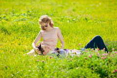 Happy young adult couple in love on the field. Two,  man and wom. Happy young adult couple in love on the field. Two,  men and women smiling and resting on the Royalty Free Stock Photo