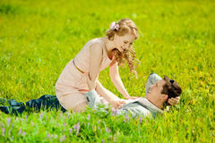 Happy young adult couple in love on the field. Two,  man and wom. Happy young adult couple in love on the field. Two,  men and women smiling and resting on the Stock Photography