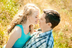 Happy young adult couple in love on the field. Two,  man and wom. Happy young adult couple in love on the field. Two,  men and women smiling and resting on the Royalty Free Stock Image