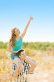 Happy young adult couple in love on the field. Two,  man and wom. Happy young adult couple in love on the field. Two,  men and women smiling and resting on the Stock Images
