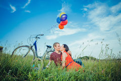 Happy young adult couple in love on the field. Two, man and woman have picnic, smiling and resting on the green grass. Royalty Free Stock Photos