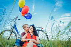 Happy young adult couple in love on the field. Two, man and woman have picnic, smiling and resting on the green grass. Royalty Free Stock Image