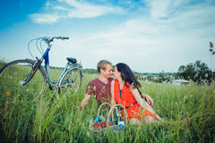 Happy young adult couple in love on the field. Two, man and woman have picnic, smiling and resting on the green grass. Royalty Free Stock Photography