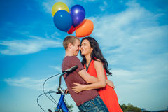 Happy young adult couple in love on the field. Two, man and woman smiling and resting after bike riding Royalty Free Stock Photo