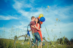 Happy young adult couple in love on the field. Two, man and woman smiling and resting after bike riding. Happy adult couple in love on the field. Two, men and Royalty Free Stock Photos