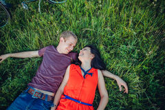 Happy young adult couple in love on the field. Two, man and woman smiling and resting on the green grass. Royalty Free Stock Image