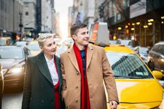Happy young adult couple walking out from yellow taxi in New York City street and looking to the side. royalty free stock photo