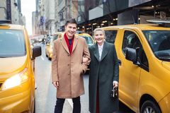 Happy young adult couple walking out from yellow taxi in New York City street for shopping. stock photography