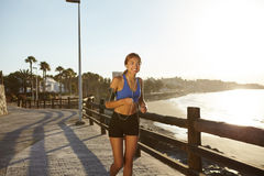 Happy young adult jogging on the beach shore Royalty Free Stock Photos