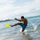 Happy young adult man playing beach ball in summer. Sand fun sport Stock Photography