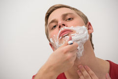 Happy young adult man shaving his face Royalty Free Stock Image