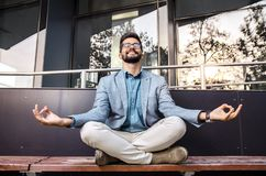 Happy young adult man in a suit meditating stock photography
