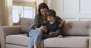 Happy mum teaching kid son learning using smartphone apps