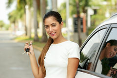 Happy young adult smiling and showing keys of new car. Young adult hispanic woman holding keys of new white car, leaning on auto door. She smiles and looks proud Royalty Free Stock Photos