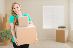 Happy Young Adult Woman Holding Moving Boxes In Empty Room In A Royalty Free Stock Images