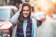 Happy young adult woman smiling with teeth smile outdoors and walking on city street at sunset time wearing winter clothes and kni Stock Photos