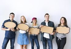 Happy young adults holding up copyspace placard thought bubbles royalty free stock photos