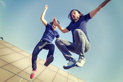 Happy young adults jumping on a terrace. Happy young adults against the sky jumping on a terrace stock photography