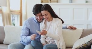 Happy young affectionate couple watching funny videos in social network.