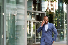 Happy young african american businessman talking on cell phone royalty free stock photography