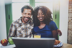 Happy young african american couple having online conversation together via touch tablet at the morning in living room Royalty Free Stock Image