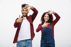 Happy young African American couple looking through a finger frame and smiling while standing isolated on white. Stock Photos