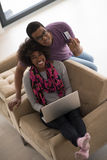 African american couple shopping online. Happy young african american couple shopping online through laptop using credit card at home Royalty Free Stock Images