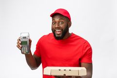 Happy young African American delivery man holding up an electronic card payment machine and delivery product. Isolated. Happy young African American delivery man stock photos