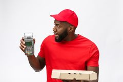 Happy young African American delivery man holding up an electronic card payment machine and delivery product. Isolated. Happy young African American delivery man stock images