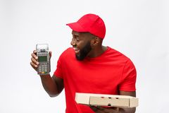 Happy young African American delivery man holding up an electronic card payment machine and delivery product. Isolated. Happy young African American delivery man stock photo