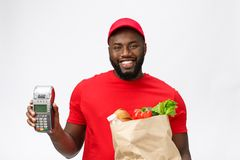 Happy young African American delivery man holding up an electronic card payment machine and delivery product. Isolated. Over grey background stock photos