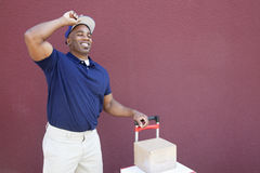 Happy young African American delivery man standing with handtruck over colored background Stock Photography