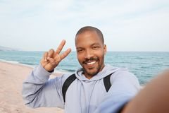 Happy young African-American hipster man taking selfie and making hand victory symbol on the beach. Cloudy sky on Royalty Free Stock Photo
