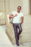 Happy young African American man carrying shoulder bag, travelin. Street Fashion. Young African American man wearing white V neck T shirt, black pants, leather Stock Photography