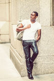 Happy young African American man carrying shoulder bag, travelin. Street Fashion. Young African American man wearing white V neck T shirt, black pants, leather Stock Images