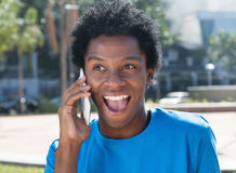 Happy young african american man at cellphone Stock Images