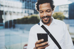 Happy young African American man in headphone walking at sunny city and enjoying to listen to music on his smart phone Stock Image