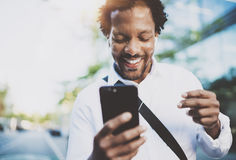 Happy young African American man in headphone walking at sunny city and enjoying to listen to music on his smartphone Stock Image