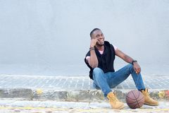 Happy young african american man sitting with basketball Royalty Free Stock Images