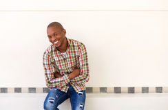 Happy young african american man sitting with his arms crossed Stock Images