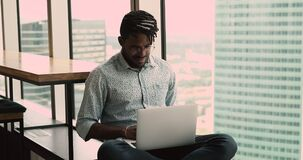 Happy young african american man working on computer, sitting on windowsill.