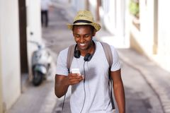 Happy young african american man walking mobile phone Stock Photography
