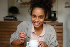 Happy young african american woman with cup of coffee Stock Photos