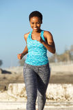 Happy young african american woman running outside Stock Image