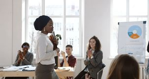 Happy young African business woman in head wrap walking along modern office, welcomed and cheered by clapping colleagues stock footage