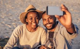 Happy young African couple taking selfies together at the beach. Smiling young African couple sitting together on a sandy beach enjoying a glass of wine and Stock Images