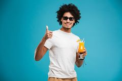 Happy young african curly man drinking cocktail showing thumbs up. Image of happy young african curly man isolated over blue wall background drinking cocktail Stock Photo