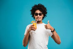 Happy young african curly man drinking cocktail showing thumbs up. Image of happy young african curly man isolated over blue wall background drinking cocktail Stock Image
